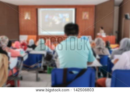 blur blurred university student sitting in a lecture room a teacher in front of the class with white projector slide scree