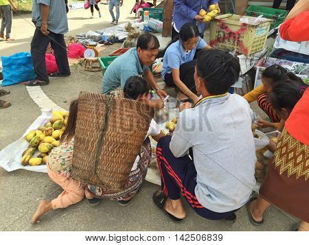 CHIANG RAI THAILAND - AUGUST 9 : horizontal photo of unidentified people buying mangoes in a market at the Thai-Laos frontier on August 9 2016 in Chiang rai Thailand. This is one of travel attraction in Chiang Rai.