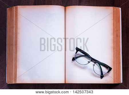 Close up notebook and eyeglasses on wooden background