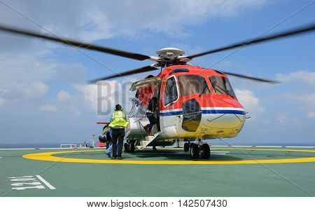 The officer take care passenger to embark helicopter at oil rig platform