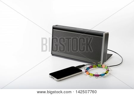 smart mobile phone connect with portable speaker for playing music on white background