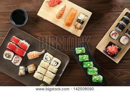 Delicious sushi set on ceramic plate and wooden boards