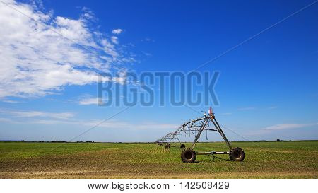 Sprinkler irrigation system on agriculture field with clear blue sky