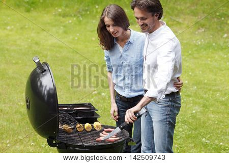 Happy couple cooking food on barbecue outdoors