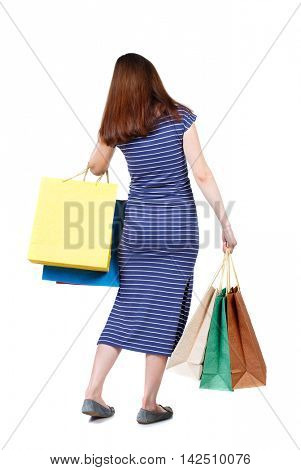 back view of woman with shopping bags. backside view of person.  Rear view people collection. Isolated over white background. The brunette in a blue striped dress holding bags presses.