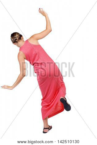 Balancing young woman.  or dodge falling woman. Rear view people collection.  backside view of person.  Isolated over white background. A slender woman in a long red dress is trying to stand on the