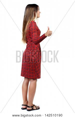 Back view of  woman thumbs up. Rear view people collection. backside view of person. Isolated over white background. The girl in red plaid dress standing cancer and shows thumb up.