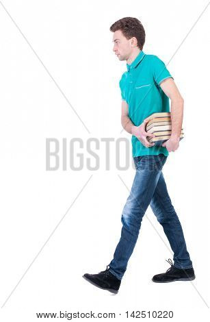 side view of going  man carries a stack of books. walking young guy . Rear view people collection.  backside view of person.  Isolated over white background. Curly kid in a turquoise jacket carries