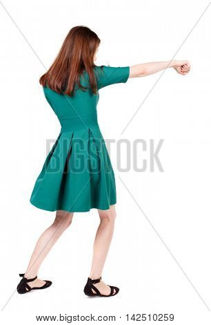 skinny woman funny fights waving his arms and legs. Isolated over white background. The slender brunette in a green short dress has outstretched arm.