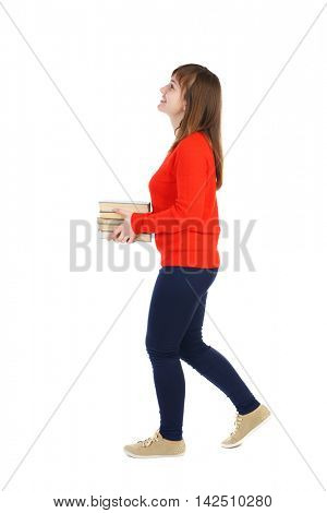Girl comes with  stack of books. side view. Rear view people collection.  backside view of person.  Isolated over white background.  Laughing girl in a turquoise jacket carries a stack of books.