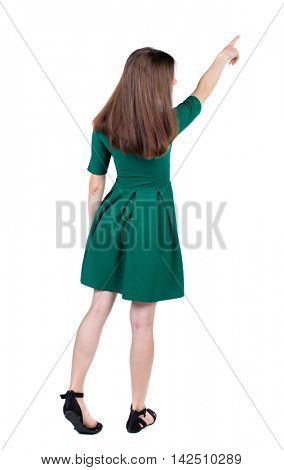 Back view of  pointing woman. beautiful girl. Rear view people collection.  backside view of person.  Isolated over white background. The slender brunette in a green short dress is pointing the index