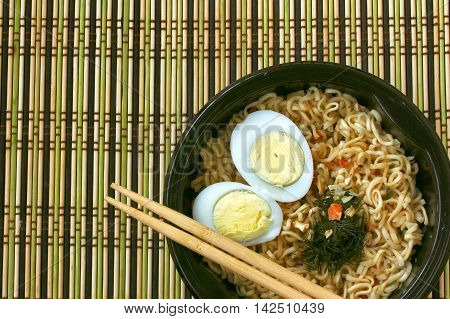 fast noodles boiled egg in black bowl with chopsticks on mat chinese food