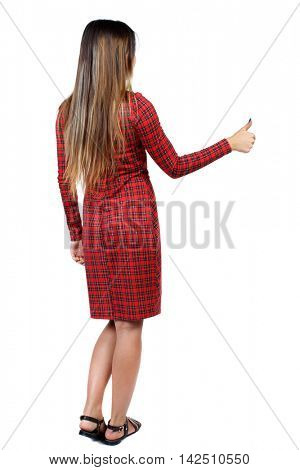 Back view of  woman thumbs up. Rear view people collection. backside view of person. Isolated over white background. The girl in red plaid dress shows thumb up.