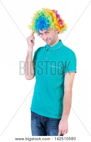 Portrait of a man in a clown wig. guy silly smiles. Isolated over white background The clown in colored wig looks shyly into the frame.