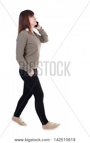 side view of a woman walking with a mobile phone. back view of girl in motion.  backside view of person.  Rear view people collection. Isolated over white background. She goes right on the phone