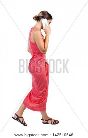 side view of a woman walking with a mobile phone. beautiful girl in motion.  backside view of person.  Rear view people collection. Isolated over white background. A slender woman in a long red dress