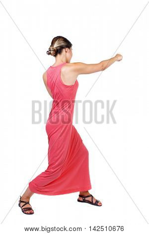 skinny woman funny fights waving his arms and legs. Isolated over white background. A slender woman in a long red dress strikes a hand.