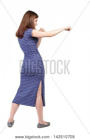 skinny woman funny fights waving his arms and legs. Isolated over white background. The brunette in a blue striped dress stands sideways and hit his foot.