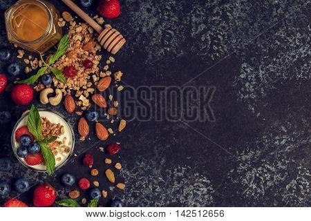 Tasty ingredients (granola honey berries yogurt and nuts) for breakfast top view. Healthy food Diet Detox Clean Eating or Vegetarian concept.