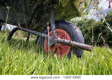 A full garden wheel barrow on long grass. Taken from a low view point showing the wheel.