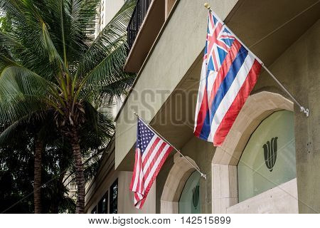 Honolulu, Hawaii, USA - Dec 21, 2015: Flags of the United States of America (USA) and Hawaii protruding from the side of a building. Image taken from the sidewalk.