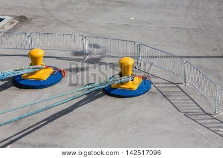 Blue ropes to yellow bollards on a concrete pier