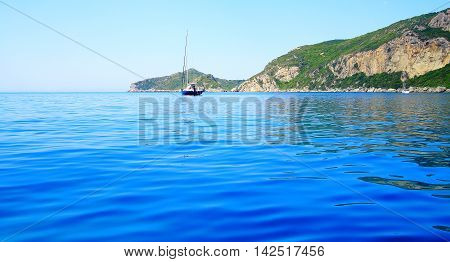 View On A Coast With A Mountain Chain And A Boat In The Mediterranean Sea On The Island Corfu (nearb