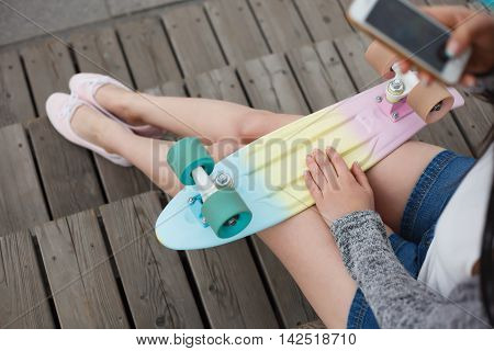 Young girl taking photo of her colorful cruiser penny skateboard and her legs while sitting outdoors. Trendy skateboarding deck and mobile phone