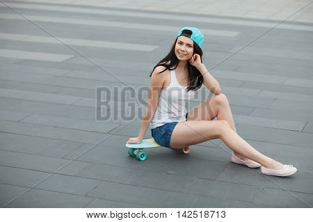 Young Girl Sitting On Short Cruiser Skateboard Outdoors
