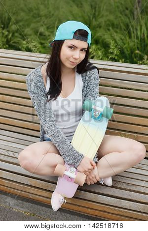 Girl Sitting On Bench With Short Cruiser Skateboard