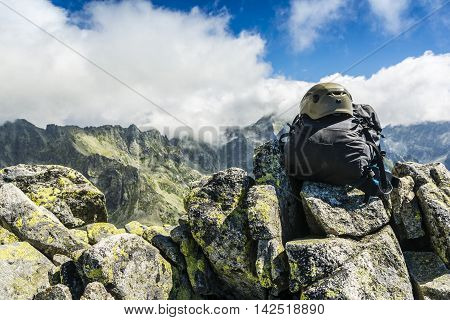 Black backpack with helmet on the summit and clouds over the ridge.