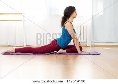 Young brunette fit woman doing daily yoga on floor mat in gym
