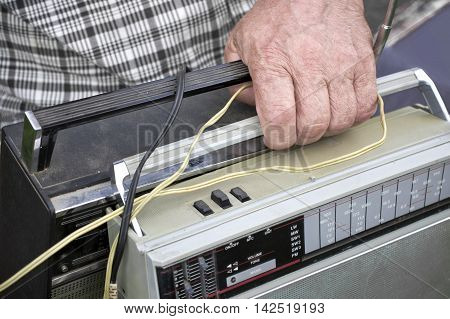 Male hand with two looking retro radio concept of breaking news.Outdoor cropped shot