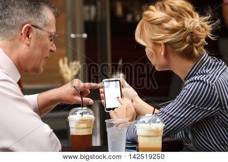 Business lunch outdoors. Senior businessman showing his colleague information on big touchscreen smart phone.