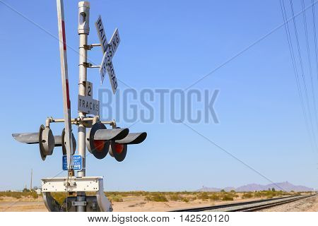 Railroad crossing in the Sonoran Desert Arizona USA secured by railroad gates and lights.