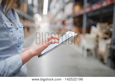 beautiful young furniture store store worker stock taking.