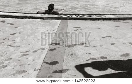 Girl in the pool a shadow man and traces of wet feet on the floor. black and white photo