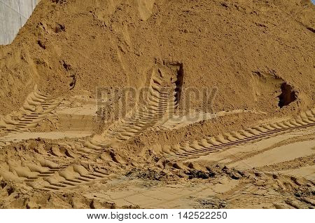 Tire tracks of heavy equipment are evident on the sand of a huge pile to be used in a construction site.