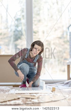 Single young adult woman in overalls working on floor with old furniture or projects in home.