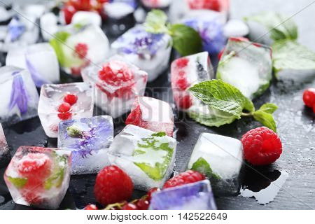 Ice Cubes With Raspberries And Mint Leaf On Wooden Table
