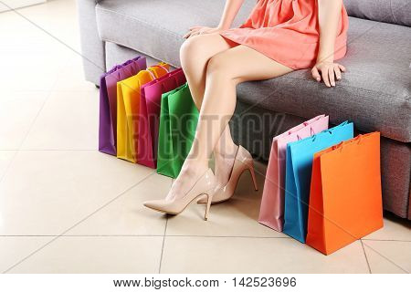 Female Legs With Beige High Heels And Shopping Bags On Grey Sofa