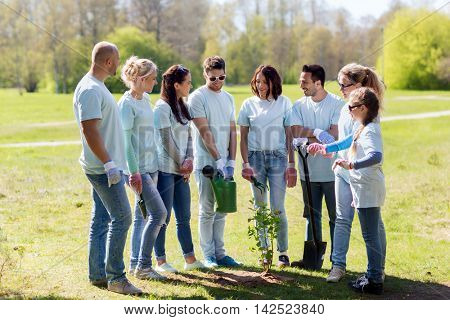 volunteering, charity, people and ecology concept - group of happy volunteers with watering can and shovel planting tree in park
