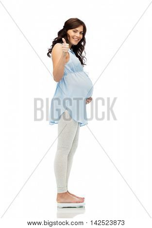 pregnancy, health care, gesture and people concept - happy pregnant woman measuring weight on scales and showing thumbs up over white background