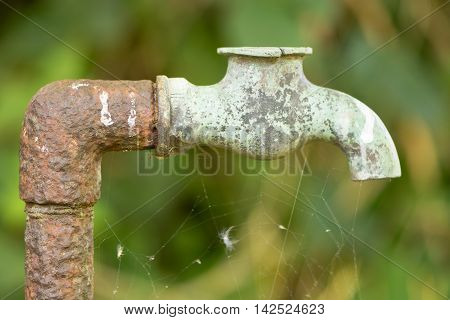 Old rusty pipe with hole and broken tap. Outdoor plumbing after many years exposed to the elements showing corrosion