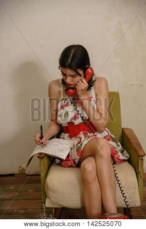 A brunette is talking on the phone and writing something down