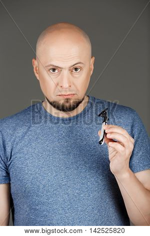 Portrait of handsome middle-aged man in grey shirt holding razor over dark background. Copy space.