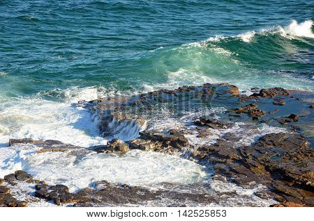 Surging waves over a tessellated rock platform weathered by ocean waves on the New South Wales coast, Australia
