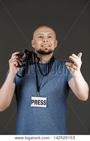 Portrait of handsome middle-aged man in grey shirt with photocamera and press badge taking pictures over dark background. Copy space.
