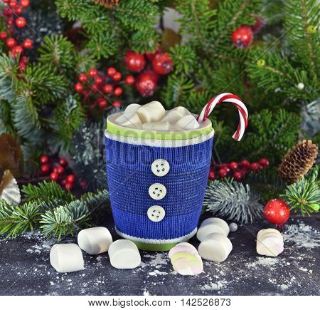 Still life with cozy knitted blue cup with Christmas drink, marshmallow and sweet cane. Winter and Christmas time close up with natural conifer, red berries and cocoa, tea or coffee