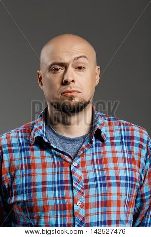 Portrait of confident surprised handsome middle-aged man in plaid shirt over grey background. Copy space.
